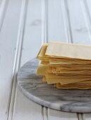 Gestapelte Lasagneblätter auf Marmorplatte