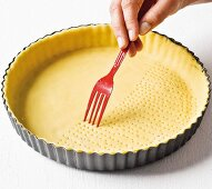 Shortcrust pastry being pierced with a fork for blind baking
