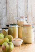 Jars of apple sauce and fresh apples
