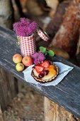 A fruit tartlet on a wooden bench in a garden