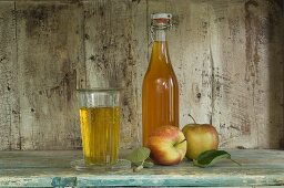 A bottle and a glass of apple juice and Jonagold apples on a rustic shelf