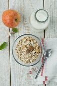 A healthy breakfast: muesli with nuts, apple and milk on a wooden table
