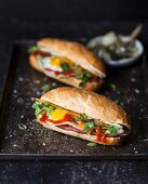 Two Bahn Mi (Vietnamese sandwiches) with ham, vegetables and fried egg
