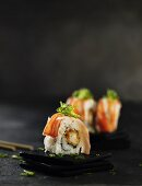 Sushi rolls garnished with seaweed on small slate dishes