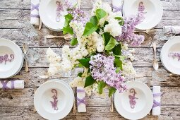 A festively laid spring table with a bunch of lilac (seen from above)