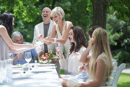 A summer family garden party: a woman serving salad