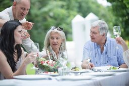 A family eating together at a table in a summer garden