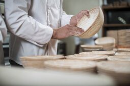 A baker dusting wicker bread baking baskets with flour