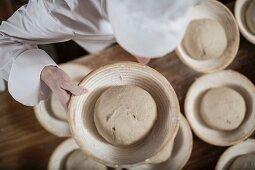 A baker making bread: bread dough being placed in wicker baking baskets
