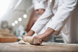 A baker making bread: rolling out dough