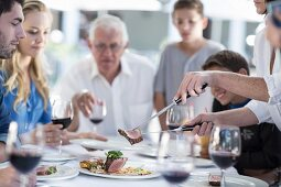 A family eating together outside: a person carving and serving meat