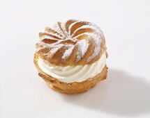 A profiterole with cream and icing sugar