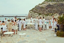 Wedding guests at a pool party on a terrace by the sea