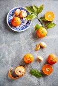 Fresh clementines, whole, peeled and with leaves