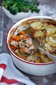 A hot pot with pork and potatoes