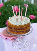 A birthday cake with blown out candles on a table outside