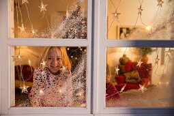 Girl looking out of window decorated with artificial snow and fairy lights