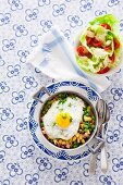 Fried potatoes with peas, bacon and fried egg