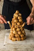 A croquembouche being decorated with caramel threads