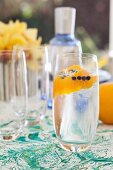Gin and tonic with decorative orange zest and juniper berries