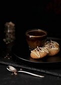 Three hazelnut cookies filled with ganache on a plate with a cup of coffee