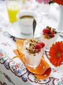 Breakfast muesli on yoghurt served with coffee and juice