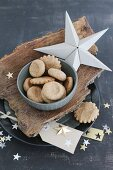 Christmas biscuits in bowl on piece of bark and stars hand-crafted from paper and gold foil