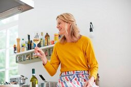 A woman holding a glass of wine in a kitchen