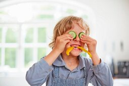 A boy playing with vegetables in a kitchen