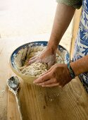 A person kneading a bowl of dough