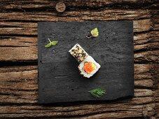 Uramaki with salmon, caviar and sesame seeds