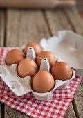 Six brown hen's eggs in an open egg box