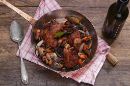 Coq au vin in a copper pan on a wooden surface