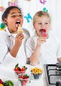 Two little girls licking homemade ice cream