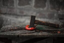 A squashed tomato with a hammer on a wooden table