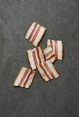 Six rashers of smoky bacon on a grey surface (seen from above)