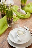 Place setting with white Easter egg in napkin nest