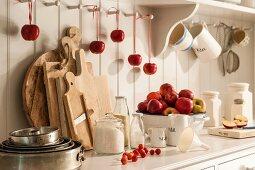 Fresh apples, baking ingredients and various kitchen utensils on dresser