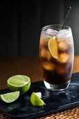 A Cuba Libre with ice cubes and limes
