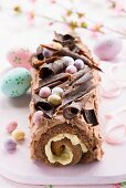 An Easter chocolate log cake with chocolate cream and Easter eggs