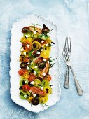 Colourful tomato salad with olives, diced mozzarella and basil