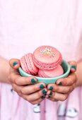 Kleines Mädchen hält eine Schale mit Himbeer-Macarons mit Zuckerperlen