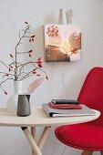 DIY-Wandleuchte aus Schaukasten mit Foto, davor Tisch mit rotem Stuhl