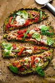 A broccoli pizza base topped with tomatoes, salami, rockets, basil, onions and mozzarella