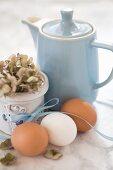 Hühnereier mit Dekoband, Hortensie und blaue Kaffeekanne auf Marmoruntergrund