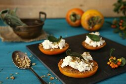 Persimmon slices with goat's cheese, sage, black pepper and hazelnuts