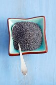 A bowl of poppy seeds with a spoon