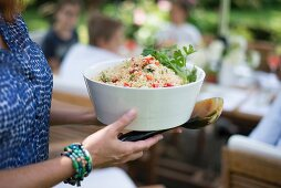 Woman holding white bowl of couscous salad