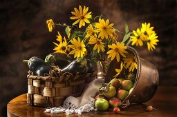 An arrangement of aubergines, apples and yellow flowers