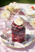 A jar of berry jam on a garden table